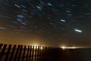 sterrensporen boven houten golbreker; start trails above wooden breakwater